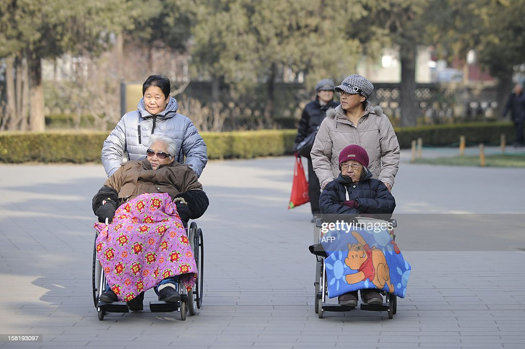 Two elderly people are pushed on their wheelchairs at a park in Beijing on December 11,2012. China's elderly face increasing uncertainty three decades since the one-child policy took hold, with no real social safety net, the law has left four grandparents and two parents with one caretaker for old age -- and bereaved families with none.