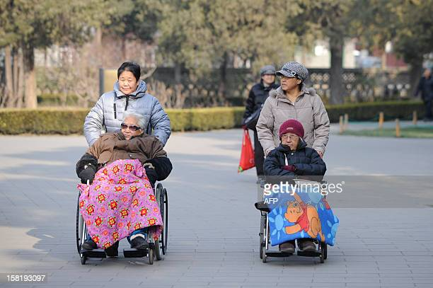 Two elderly people are pushed on their wheelchairs at a park in Beijing on December 112012 China's elderly face increasing uncertainty three decades...