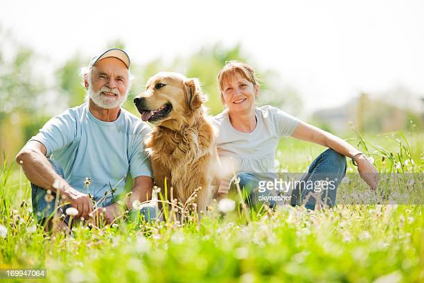Two elderly people with their dog in the park.