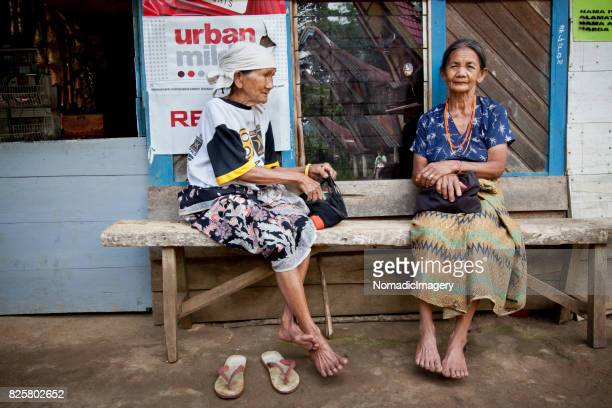 Two elderly tribal ladies seated on bench in Toraja