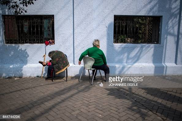 TOPSHOT Two elderly women enjoy the sun in front of a wall in Shanghai on February 24 2017 / AFP / Johannes EISELE