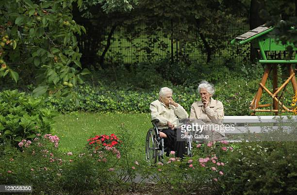 Two elderly women sit and chat in the gardens of the Sewanstrasse senior care home in Lichtenberg district on August 30 2011 in Berlin Germany The...