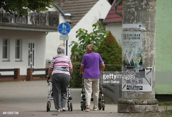 Two elderly women walk along a street on July 15 2015 in Altdoebern Germany Altdoebern is located in a region where openpit coal mines once abounded...