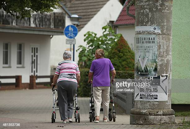 Two elderly women walk along a street on July 15 2015 in Altdoebern Germany Altdoebern is located in a region where openpit coal mines once abounded...