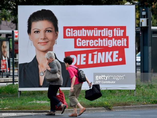 Two elderly women walk past a placard featuring the Left Party's main candidate Sarah Wagenknecht in Berlin on September 20 ahead of parliamentary...