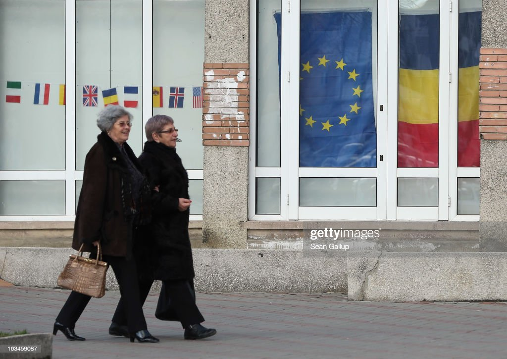 Two elderly women walk past a storefront displaying the European Union and Romanian flags on March 10, 2013 in Pitesti, Romania. Both Romania and Bulgaria have been members of the European Union since 2007 and restrictions on their citizens' right to work within the EU are scheduled to end by the end of this year. However Germany's interior minister announced recently that he would veto the two countries' entry into the Schengen Agreement, which would not affect labour rights but would prevent passport-free travel.
