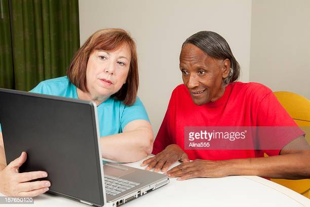 Two elderly women working on a laptop