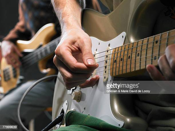 Two electric guitar players close up on hands.