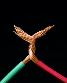 Two electrical cables with copper wires twisted together, close-up
