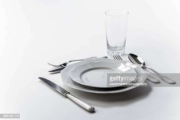 Two elegant white plates, silverware, and a glass