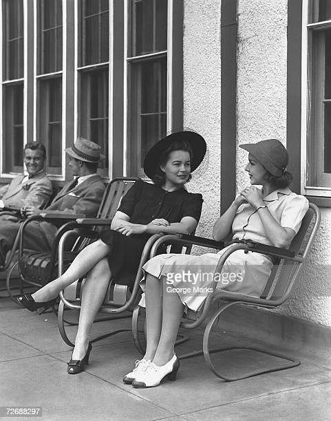 Two elegant women sitting on armchairs outdoors, (B&W)