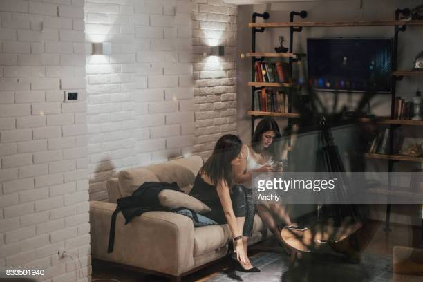 Two elegant young woman sitting on the sofa