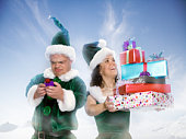 Two 'Elves' holding christmas presents outdoors (digital composite)