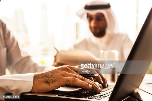 Two Emirates business men filling documents in a cafe