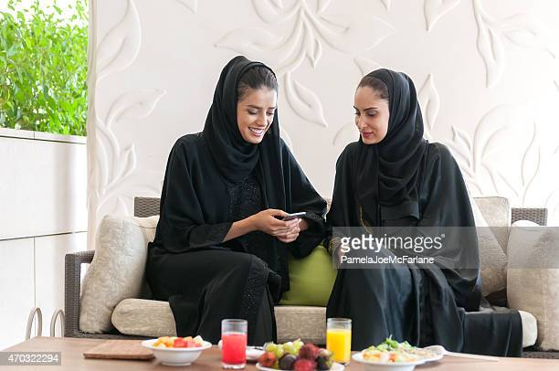 Two Emirati Women in Abaya Texting on Cellphone at Lunch