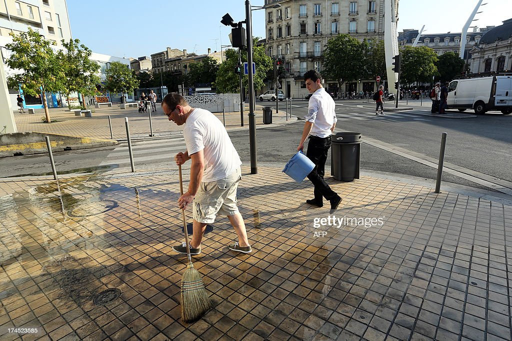Two employees clean the entrance of their restaurant on July 27, 2013 in Bordeaux, after violent storms hit southwestern France overnight. AFP PHOTO / NICOLAS TUCAT
