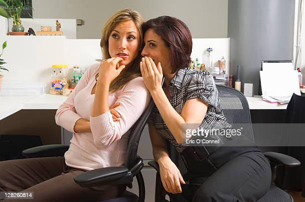 Two employees gossiping in office cubicle