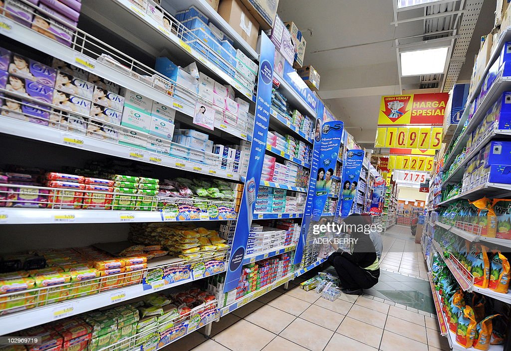 Two employees of the Indonesia subsidiary of French supermarket chain Carrefour stock shelves at one of the company's supermarkets in Jakarta on...