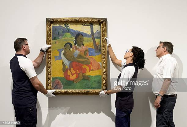 Two employees of the Reina Sofia Museum install Paul Gauguin's 'Nafea Ipoipo faa' the most expensive painting ever sold in Madrid on July 3 2015...