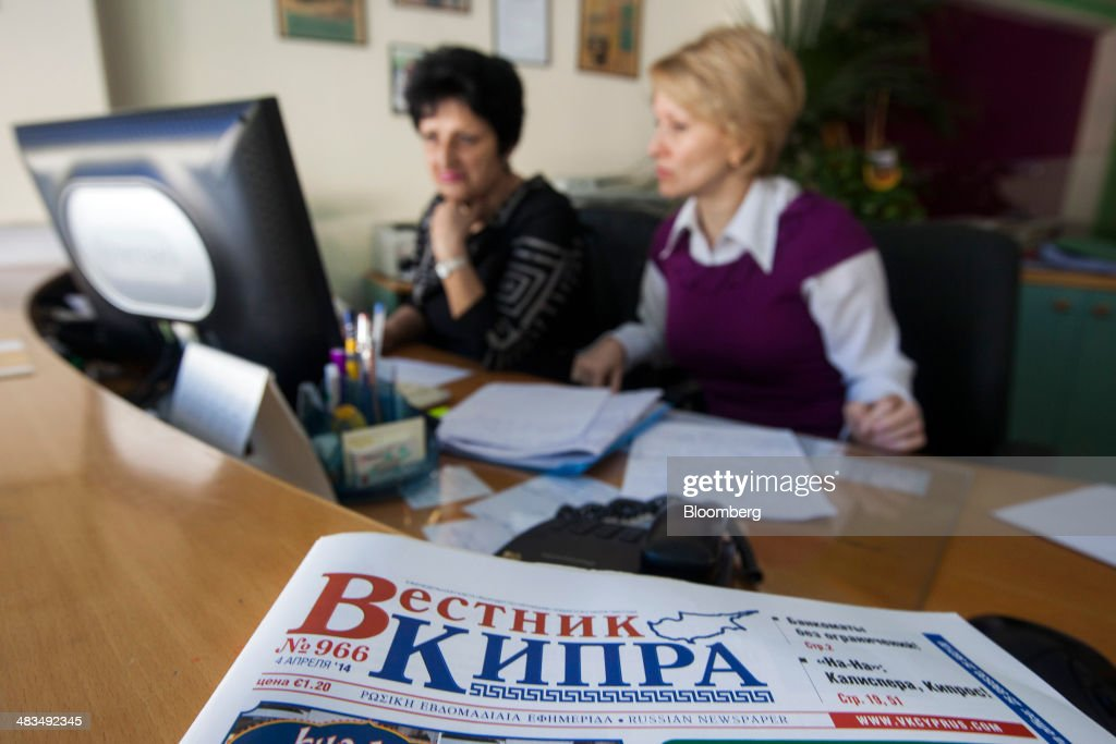 Two employees work at a desk in the Russian newspaper offices of Vestnik Kipra in Limassol, Cyprus, on Tuesday, April 8, 2014. Cyprus wants to shield financial flows with Russia, where it's the biggest foreign investor, as the U.S. and the European Union ratchet up sanctions in response to President Vladimir Putin's annexing Crimea from Ukraine. Photographer: Andrew Caballero-Reynolds/Bloomberg via Getty Images