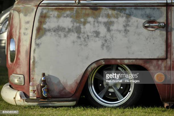 Two empty beer bottles sit on the front bumper on a very low and 'ratty' early VW Baywindow Type 2 Transporter at Vanfest festival in the Three...