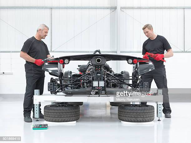 Two engineers assembling supercar in sports car factory
