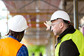 Two architects wearing hardhat and safety jacket pointing at scaffolding on construction site
