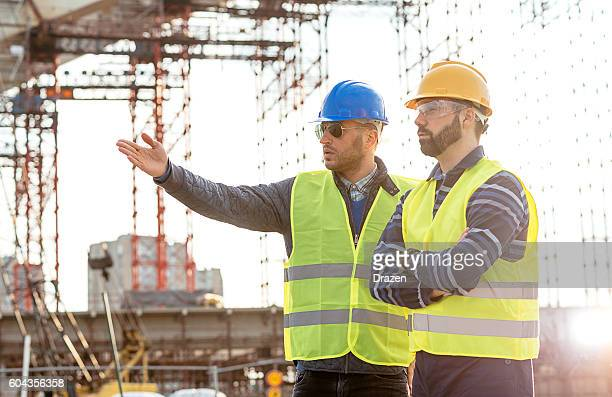 Two engineers discussing construction works on site