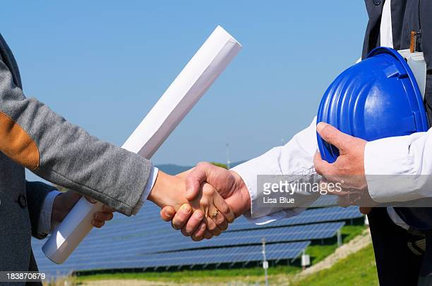 Two Engineers Handshaking in Solar Power Station