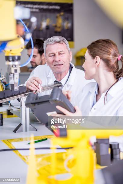 Two engineers in factory talking about device