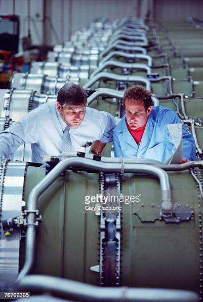 Two engineers in jet engine manufacturing plant