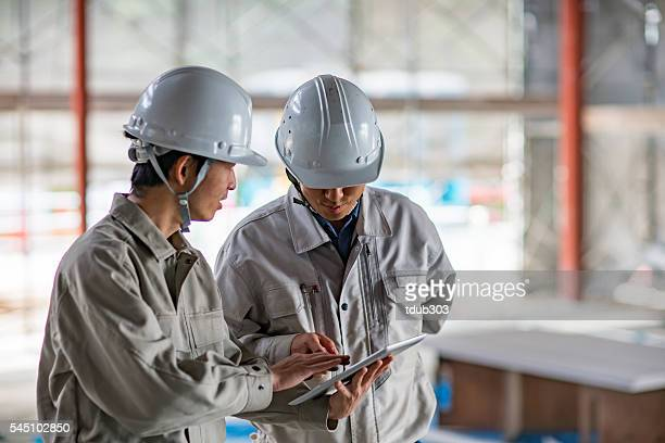 Two engineers looking at a digital tablet at building site