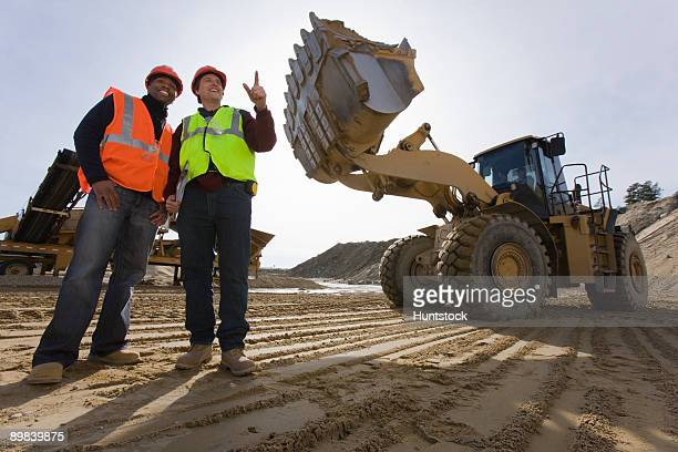 Two engineers near a front-end loader at an asphalt plant