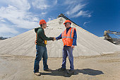 Two engineers shaking hands at a gravel and asphalt plant