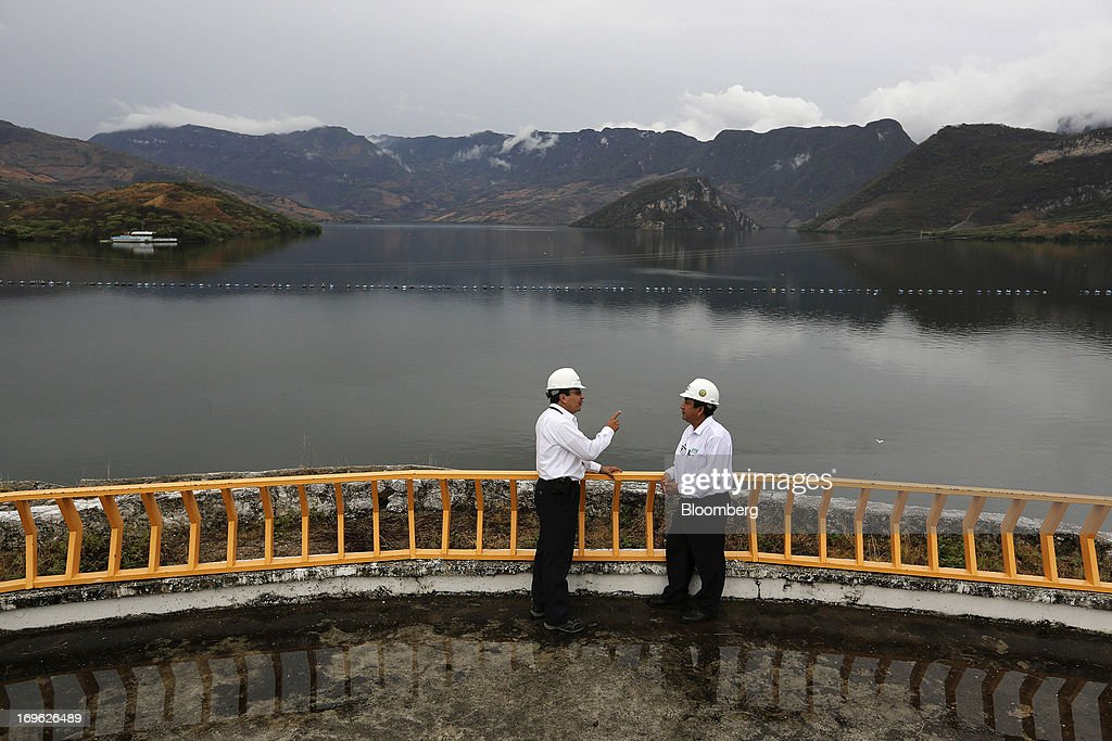 Two engineers speaks on an embankment at the Comision Federal de Electricidad's (CFE) Manuel M. Torres Dam and hydroelectric power station in the state of Chiapas near Chicoasen, Mexico, on Monday, May 27, 2013. CFE, Latin America's biggest utility, is trying to capitalize on investor demand that's made Mexico the world's best-performing government bond market to borrow pesos at record-low interest rates. Photographer: Susana Gonzalez/Bloomberg via Getty Images
