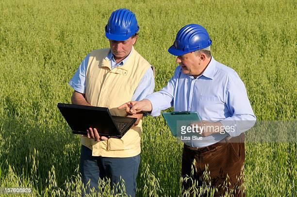 Zwei Ingenieure mit PC in der Landschaft