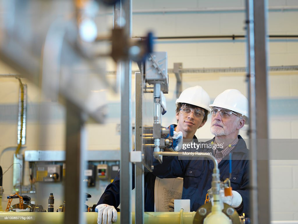 Two engineers working behind machinery : Stock Photo