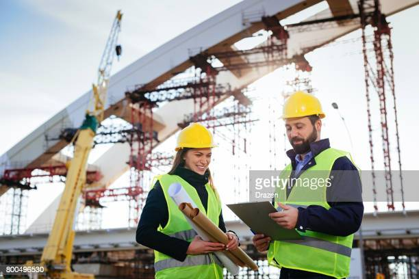 Two engineers working together on construction site with blueprints and plans