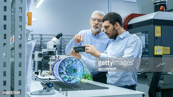 Two Engineers Works with Mobile Phone Using Augmented Reality Holographic Projection 3D Model of the Engine Turbine Prototype. Development of Virtual Mixed Reality Application. : Stock Photo