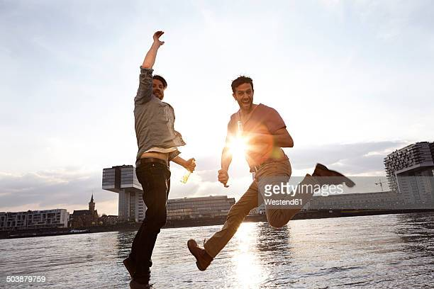 Two enthusiastic with beer bottles on riverbank