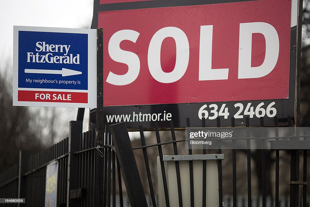 Two estate agents signs advertise residential property as 'Sold' and 'For Sale' on railings outside the buildings in Dublin, Ireland, on Sunday, March 17, 2013. Ireland's renewed competiveness makes it a beacon for the U.S. companies such as EBay, Google Inc. and Facebook Inc., which have expanded their operations in the country over the past two years. Photographer: Simon Dawson/Bloomberg via Getty Images