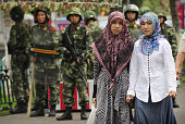 Two ethnic Uighur women pass Chinese paramilitary policemen standing guard outside the Grand Bazaar in the Uighur district of the city of Urumqi in...