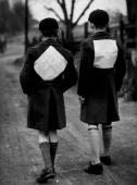 Two evacuees wear white paper pinned on their backs during a walk along country roads after blackout time