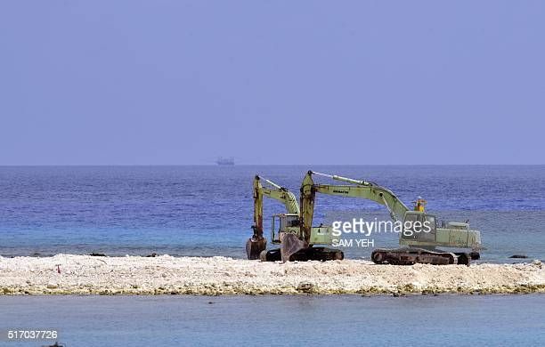 Two excavators are pictured at a construction site on Taiping island in the Spratly chain in the South China Sea on March 23 2016 Taiwan on March 23...