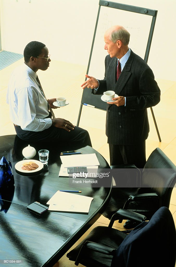 Two executives in informal discussion during presentation : Stock Photo