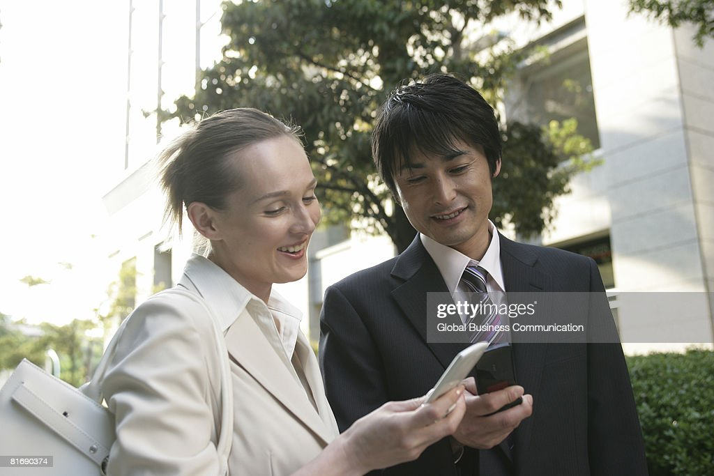 Two executives with mobile phones, smiling : Stock Photo