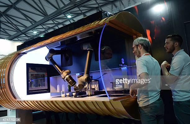 Two exhibitors demonstrate a kitchen robot from Moley Robotics to visitors during the first Consumer Electronics Show in Asia in Shanghai on May 26...