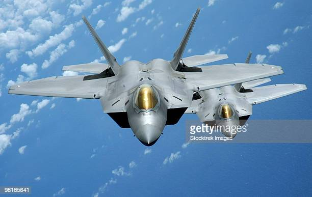 Two F-22 Raptors fly over the Pacific Ocean.