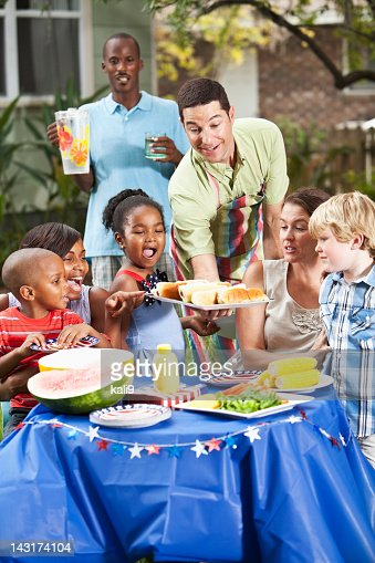 Two families at backyard cookout : Stock Photo