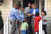 Two families greeting each other on porch with pie